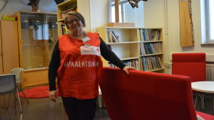 Kvinna i röd röda-korset väst i ett skolbibliotek