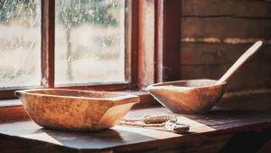 Kaksi puuastiaa puupöydällä joitten päälle aurinko paistaa ikkunasta.