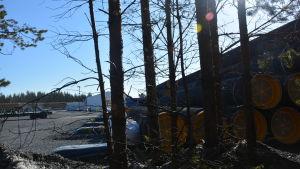 Bild på rör inne på ett industriområde. I förgrunden syns träd