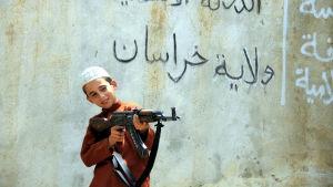 Ett barn i IS leker med automatvapen.