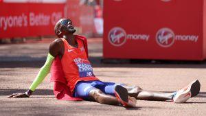 Mo Farah ligger på marken efter ett maratonlopp.