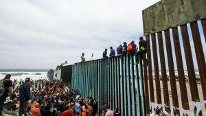 Migranter samlade i Tijuana vid gränsmuren mellan Mexiko och USA