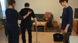 Pirkko Paananen övar sig på att gå med en såkallad fyrpunktskäpp. Terapeuterna Susanne Miikki och Anna Cederborg finns där som stöd.