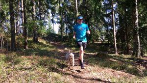 Mies juoksee koiran kanssa metsässä