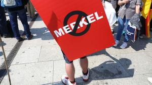 Ett anti-Merkel-plakat under AfD:s demonstration i Berlin i maj 2018.