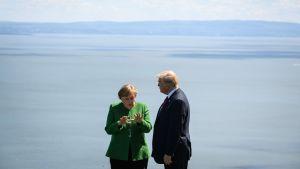 Donald Trump och Angela Merkel framför öppet hav i Kanada