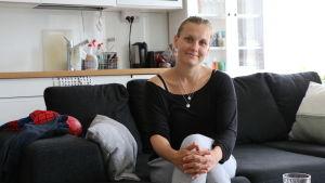 föräldern malin gullqvist sitter i soffan hemma hos sig med ett vitt kök i bakgrunden.