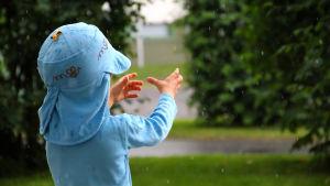 Ett litet barn fösöker fånga regnet med händerna.