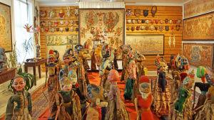 konstutställning med ett rum fyllt av tavlor och dockor och masker