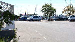 Parkeringsplats med några bilar en varm sommardag. Hav och båtar i bakgrunden.