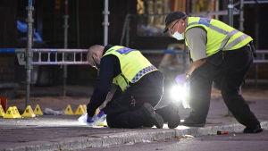 Två poliser undersöker något på marken vid några byggställningar.