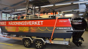 en röd och silverfärgad aluminiumbåt på en trailer inne i en brandstation. Står Räddningsverket längs båtens långsida. Båten har två utombordsmotorer.