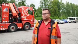 En man står i förgrunden iklädd röd t-skjorta och reflexväst. Han har glasögon. I bakgrunden syns en lastbil som kan bärga bilar och bakom den skog.