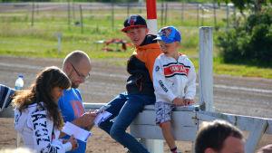 En familj som följer med tävlingen och står fast vid staketet. Två barn sitter på staketet.