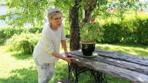 """Margareta """"Teta"""" Reinlund inspekterar ett bastant trädgårdsbord"""