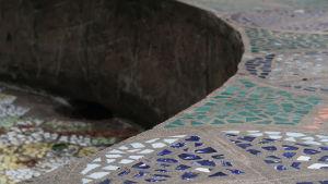 Mosaikmönster i mörkblått, grönt och vitt i en cementfärgad fontän.