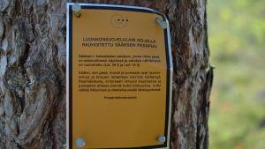 En gul skylt på ett träd informerar om att det finns ett fredat fiskgjusbo i trädet.