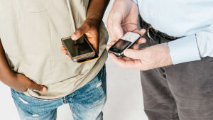 Nuoren ja vanhan ihmiset kädet: Nuorella kädessä älypuhelin, vanhalla näppäinpuhelin.