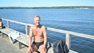 Man i badbyxor på brygga vid vattnet en varm sommardag.