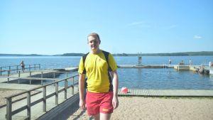 Badvakt i gul t-skjorta och röda shorts vid sandstrand. I bakgrunden en brygga.