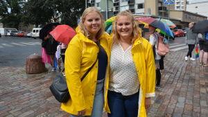 sara och ida nordell i gula regnjackor med färgglada paraplyer i bakgrunden