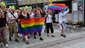 människor ropar i prideparaden i åbo och håller i sina stora regnbågsflaggor