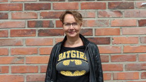 """Tutkija Tuula Juvonen kuvattuna tiiliseinän edessä. Hänen päällä on nahkatakki ja t-paita, jossa teksti """"batgirl""""."""
