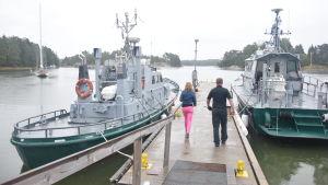 Två båtar vid en brygga, alla hör till sjöbevakningen och två personer på väg till båtarna