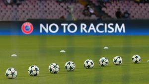 Säg nej till rasism på en fotbollsarena med bollar i förgrunden