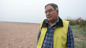 en man med blårutig flanellskjorta. Ovanpå en gul reflexväst. Han står på en sandstrand.