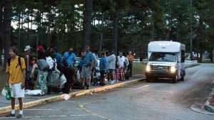 Personer som evakuerat undan orkanen Florence står på rad utanför en skola.