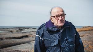 Silmälasipäinen vanhempi mies sinisessä takissa seisoo kivikkoisella rannalla meri taustalla.