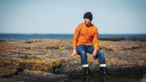 Man i svart mössa, orange ylletröja och gummistövlar sitter på klippa med stövlarna i bergsskreva fylld med vatten.