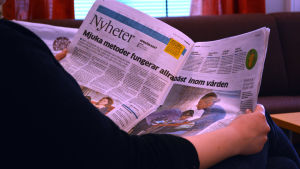 Människa som läser papperstidning.