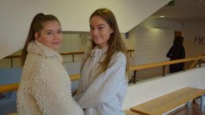 Två flickor i ljusa kläder poserar invid ett räcke.