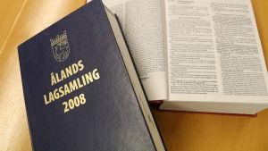 Ålands lagsamling 2008, en blå bok med guldtext på pärmen, ligger på ett brunt bord.