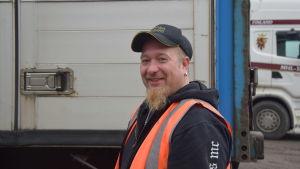 en man med keps o orangefärgad reflexväst som har en långtradare med släp bakom sig