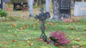 Begravningsplatsen i Sideby med ett gammalt järnkors med en rosa ljung bredvid