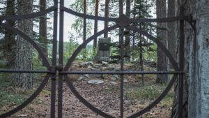 I förgrunden en järnport, i bakgrunden en gravsten på skogig tomt.