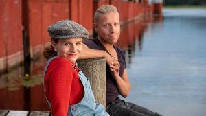 Programledarna Hannamari Hoikkala och Nicke Aldén sitter på en brygga vid en sjö, en rad med rödmålade fiskebodar i bakgrunden.