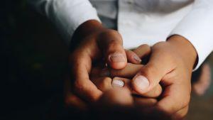Kaksi ihmistä pitämässä toisiaan kädestä.