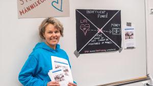 En glad kvinna står framför en tavla med plakat om människohandel.