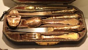 Gamla gyllene bestick i ett fodral.
