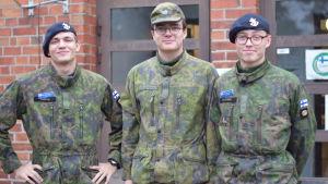 Tre beväringar i kamouflagemönstrad uniform. Står utanför en röd tegelbyggnad (Soldathemmet)