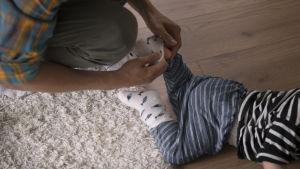 Vanhempi laittaa sukkaa lapsen jalkaan.