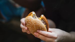 Kädet pitelevät hampurilaista.
