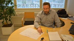Ted Bergman sitter vid sitt skrivbord med papper framför sig.