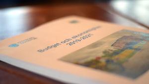 En bunt med papper på ett bord. På översta pappret finns en bild och en text där det står: Budget och ekonomiplan 2019-2021