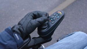 Närbild på Jonas hand som kör rullstolen