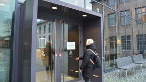 En kvinna med ljust hår sträcker sig mot en dörr in till Åbo Akademis hus Arken i Åbo.